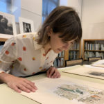 Image of IFPDA intern Jordan Hillman observing a colorful work on paper